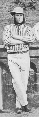 A man in a striped shirt and a bowler hat standing with his arms folded looking off camera.