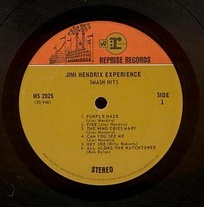 """Two-tone orange"" label used by Reprise during the Warner Bros.-Seven Arts merger from 1968 to 1969. (Label to Jimi Hendrix's Smash Hits.) After the Kinney National Company took over Warner Bros. in 1969, the orange tone at the top of the label was changed to the same tone as on the rest of the label, the W7 box logo was removed and the circled :r logo became a boxed logo without the ""Reprise"" designation."