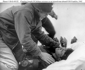 Chaplain Joseph T. O'Callahan ministers to an injured man aboard USS Franklin, 1945.