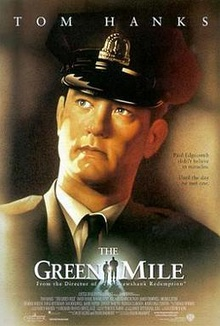 The words Tom Hanks, a prison guard looking to the distance, below the words The Green Mile, in the middle of the words, a small silhouette of a big man and small man walking towards a light.