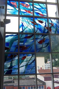 A salmon-themed stained-glass window in the Juneau Public Library expresses some of the city's heritage.