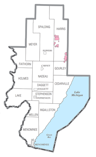 U.S. Census data map showing local municipal boundaries within Menominee County.  Gray shaded areas represent incorporated cities, and pink shaded areas represent reservations of the Hannahville Indian Community.