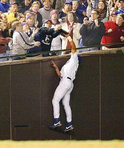 Fan Steve Bartman and Moises Alou both attempt to catch the foul ball hit by Luis Castillo during Game 6 of the 2003 NLCS at Wrigley Field in Chicago.