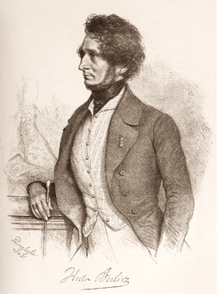 portrait of white man in early middle age, seen in left profile; he has bushy hair and a neckbeard but no moustache.